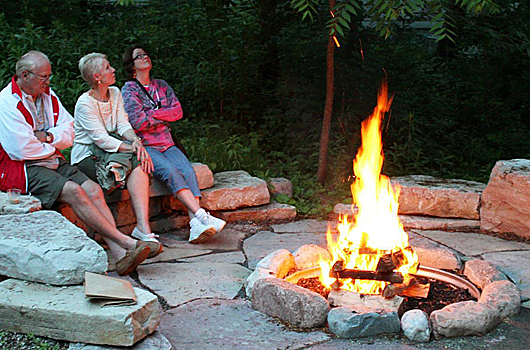 3 participants gathered around the fire pit