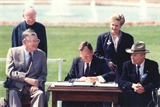 Picture of Persident George H.W. Bush signing the Americans with Disabilities Act on July 26, 1990 at an outside event.