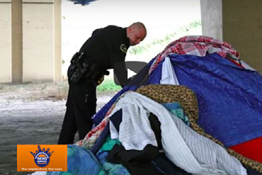 Police officer checks on homeless individual's tent