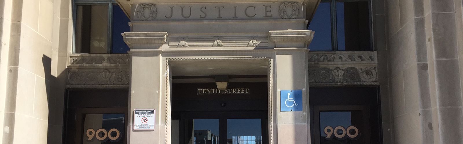 Picture of the entrance into the Courthouse. Above the doors is the word 'Justice'