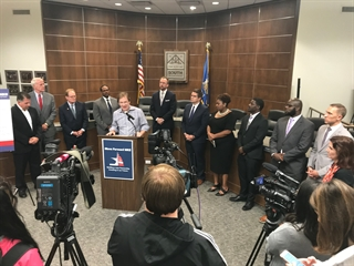 Chris Abele stands in a front of a podium, other elected leaders stand behind him to endorse a one percent sales tax increase